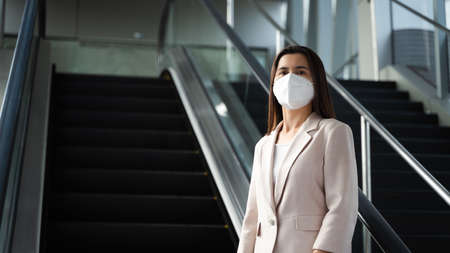 Asian woman wearing N95 face mask to protect pollution PM2.5 and virus. COVID-19 Coronavirus and Air pollution pm2.5 Healthcare and medical concept.