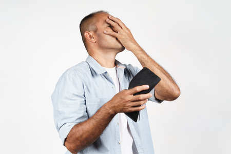 Upset mature man holding his empty wallet on white background. financial crisis, bankruptcy, no money, bad economy Concept. 免版税图像