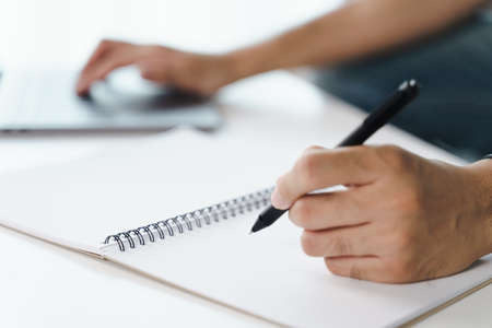 Close up of young man in casual cloth hands writing down on the notepad, notebook by ballpoint pen and using laptop computer on the table. 免版税图像