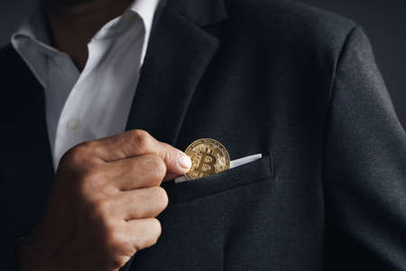 Handsome Investor Businessman put a golden bitcoin to the suit pocket on dark background, trading, Cryptocurrency, Digital virtual currency, alternative finance and investment Concept.