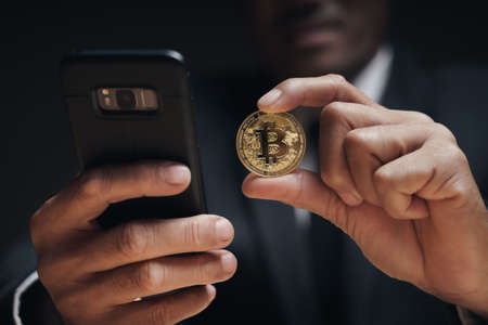 Businessman in black suit holding a golden bitcoin using Smartphone with Bitcoin trading chart on the screen to Trading Cryptocurrency, alternative finance and investment Concept. 免版税图像
