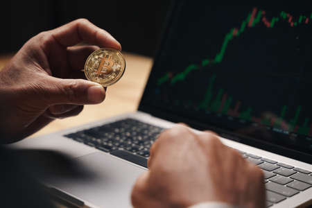 Businessman holding golden bitcoin on computer trading chart screen background. stock, cryptocurrency trading Concept. 免版税图像