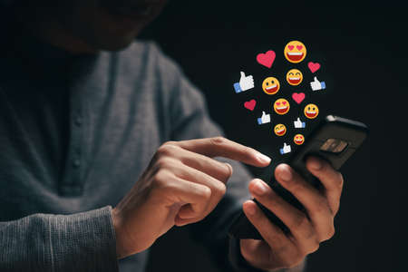 Happy young man using smartphone chatting on Social network sending Emoji, Emoticon. Social media, Live Streaming Concept.