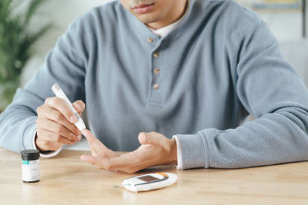 Man using lancet on finger for checking blood sugar level by Glucose meter, Healthcare and Medical, diabetes, glycemia concept