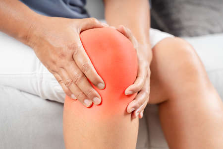 Close up of chubby woman sitting on the sofa and feeling knee pain and she massages her knee. Healthcare and medical concept.