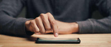 Closeup of a man using a smartphone on the wooden table, searching, browsing, social media, message, email, internet digital marketing, online shopping.
