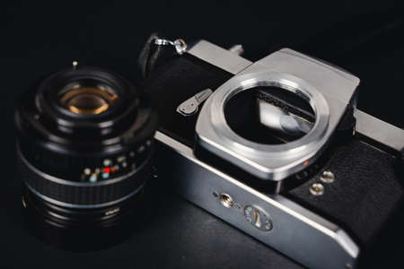 Old SLR film camera and a lens on black background, Photography Concept. 免版税图像
