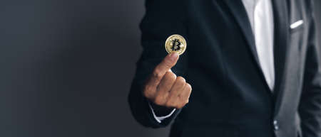 Handsome Investor Businessman in black suit holding a golden bitcoin on dark background, trading, Cryptocurrency, Digital virtual currency, alternative finance and investment Concept.