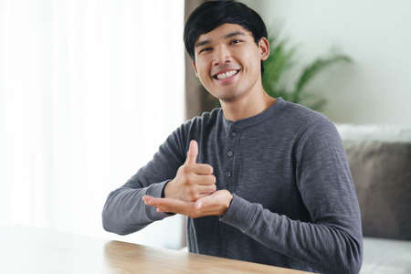 Young Asian deaf disabled man using Sign Language to communicate with other people.