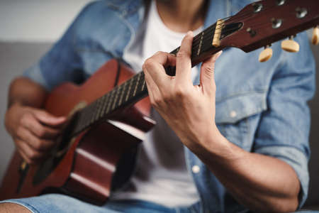 Enjoy handsome asian man practicing or playing the guitar on the sofa at living room
