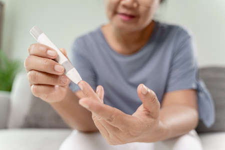 Mature Asian woman using lancet on finger for checking blood sugar level by Glucose meter, Healthcare and Medical, diabetes, glycemia concept