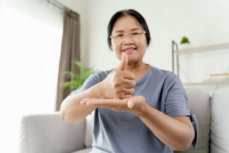 Mature Asian deaf disabled woman using Sign Language to communicate with other people. 免版税图像