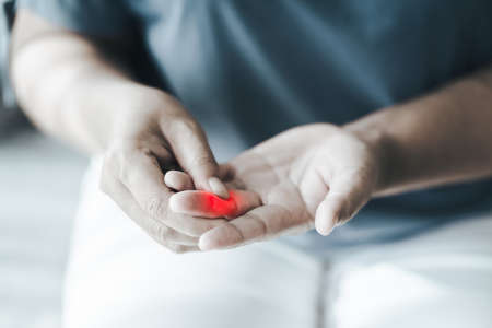 Woman suffering from hand and finger joint pain with red highlight. Causes of rheumatoid arthritis, carpal tunnel syndrome, gout. Health care and medical concept. 免版税图像