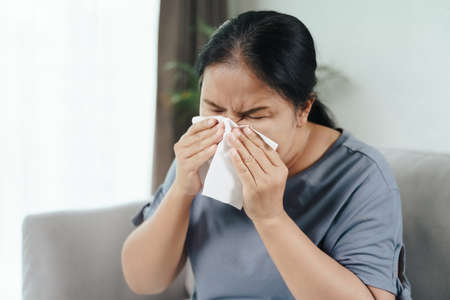 Cold sick woman got nose allergy cough or sneeze with tissue paper sitting on the sofa. Healthcare and medical concept. 免版税图像