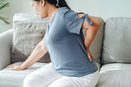 Mature woman feeling pain in her back sitting on the sofa at home. Healthcare and medical concept.
