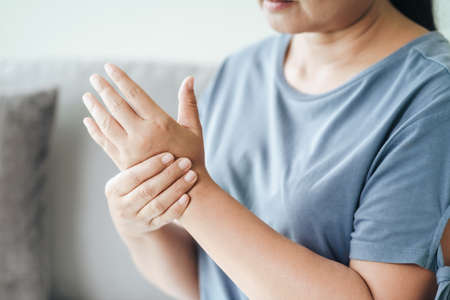 Closeup of woman sitting on sofa holds her wrist. hand injury, feeling pain. Health care and medical concept. 免版税图像