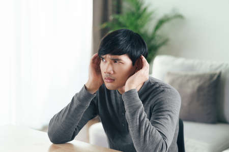 Young Asian deaf disabled man having hearing problems holds his hand over the ear, listens carefully, hard of hearing.