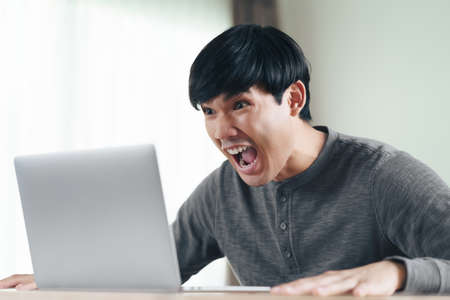 Angry shocked surprised Asian man looking at laptop computer screen sitting in the living room.