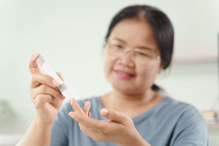 Asian woman using lancet on finger for checking blood sugar level by Glucose meter, Healthcare and Medical, diabetes, glycemia concept