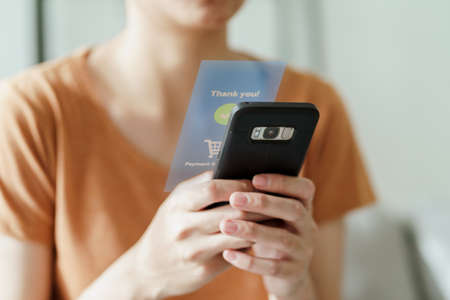 Young woman using smart phone for online shopping, internet banking, e-commerce, spending money, working from home concept 免版税图像