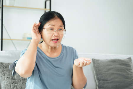Mature Asian deaf disabled woman having hearing problems holds his hand over the ear, listens carefully, hard of hearing. 免版税图像
