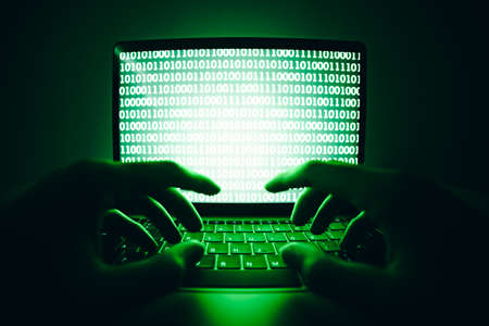 Closeup of hacker is using the laptop computer to coding virus or malware for hacking internet server, Cyber attack, System breaking, Internet crime concept.