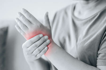 Closeup of woman sitting on sofa holds her wrist, hand injury with red highlight, feeling pain. Health care and medical concept. 免版税图像