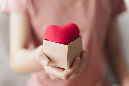 Woman holding giftbox with red heart, love, health insurance, donation, happy charity volunteer, world mental health day, world heart day, valentine's day