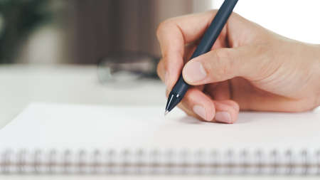 Close up of young man in casual cloth hands writing down on the notepad, notebook using ballpoint pen on the table. 免版税图像