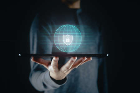 Man holding tablet with padlock shield protects security icon on the virtual display.  Cyber security safe data protection business technology privacy concept. Information security system. 免版税图像