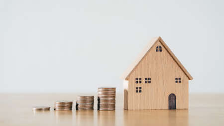 Wooden house and stacking coins on wooden table. saving money for buying house, financial plan home loan concept.