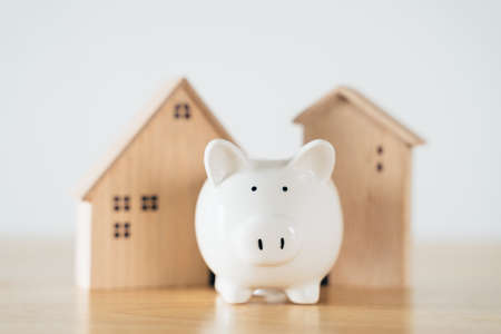 Wooden house with white piggy bank on wooden table. saving money for buying house, financial plan home loan concept.