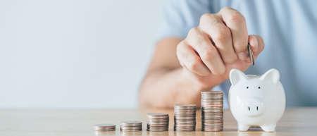 Closeup of man hand putting money coin into piggy bank for saving money. saving money and financial concept