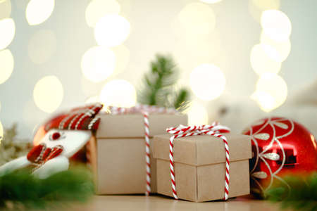 Christmas or Newyear gift box with tree branches and christmas decorations on wooden table, twinkling party lights bokeh background. 免版税图像