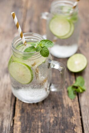 Homemade lemonade drink with fresh lime in glass on old wooden background