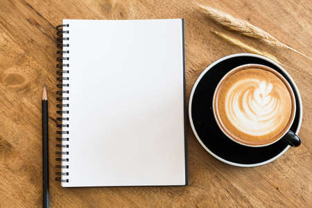 Top view empty notebook and coffee cup on wooden table top view.