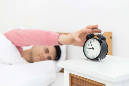 Man sleeping in bed early wake up not getting enough sleep feel irritated when they hear the alarm clock Archivio Fotografico