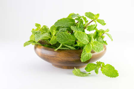 mint leaf in a wooden bowl isolated on white background