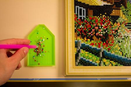 process diamond mosaic, photography, multi-colored scheme, stylus, rhinestones. needlework, hand, fingers