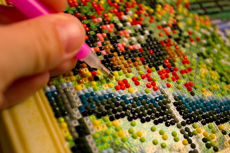 verarbeiten Diamantmosaik, Fotografie, mehrfarbiges Schema, Stift, Strasssteine. Handarbeiten, Perlen, Makro