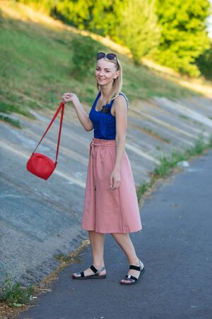 slim tall blonde girl in blue top, light pink skirt, black sandals, wearing sunglasses, with a small red shoulder bag whirling around and smiles. vertical photography.