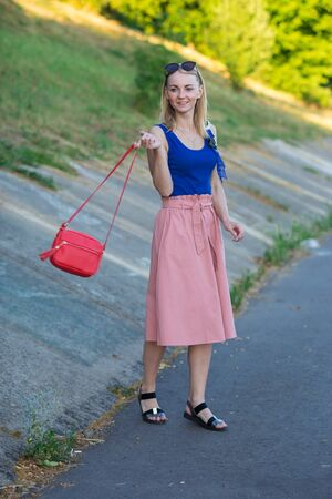 blonde girl in blue top and light pink skirt, black sandals, with a small red shoulder bag whirling around. vertical photography.