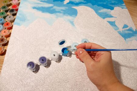 the process of dipping a brush into a jar of acrylic paint. drawing a picture by numbers. set for creativity and needlework at home.