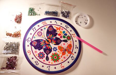 lesson diamond mosaic. set for gluing rhinestones on a butterfly picture. A lesson for the development of fine motor skills for children and adults. horizontal photo. the details Foto de archivo