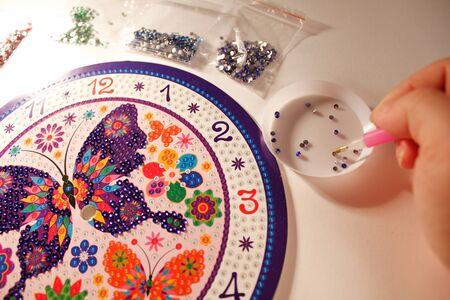 lección de mosaico de diamantes. fijado para pegar pedrería en una imagen de mariposa. Una lección para el desarrollo de la motricidad fina para niños y adultos. foto horizontal. los detalles