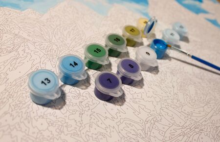 set for drawing: canvas with numbers, jars of acrylic paint, brushes. The image of a bird. Horizontal photo.