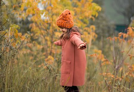 Cheerful preschooler girl in a brown coat and orange hat is spinning and spread her arms to the sides like an airplane. horizontal photo of a child in the fall Zdjęcie Seryjne