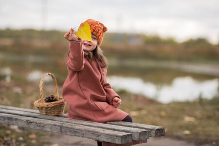yellow leaf in focus. one girl in a brown coat and an orange hat sits on a bench near the lake, smiling in blur. horizontal photograph of a child.