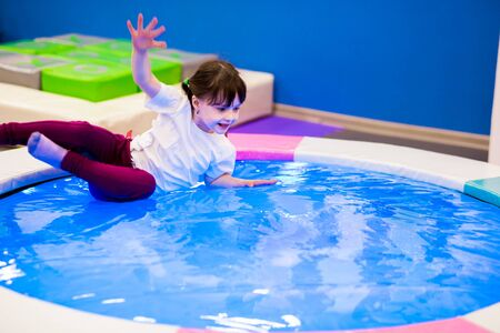 funny girl preschooler with ponytails in a white T-shirt plays, jumps on an inflatable water trampoline with backlight. entertainment in the games room Banque d'images
