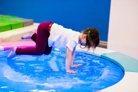 funny girl preschooler with ponytails in a white T-shirt plays, jumps on an inflatable water trampoline with backlight. entertainment in the games room.